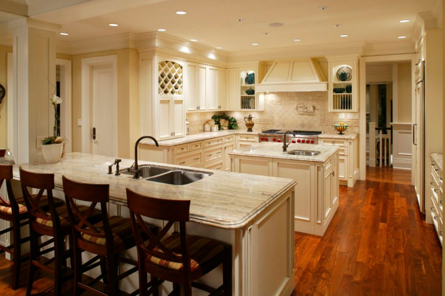 A spacious kitchen featuring hardwood floors and beige walls. It offers a square center island and a breakfast bar island with a marble countertop.