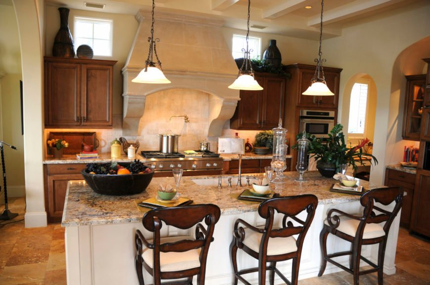 Mediterranean kitchen with beige tiles flooring and a ceiling with beams. It offers brown cabinetry and kitchen counters, along with a center island with a marble countertop.