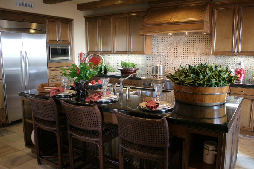 A closer look at this kitchen's island with a black countertop and has a breakfast bar. The kitchen features tiles flooring and a ceiling with beams.