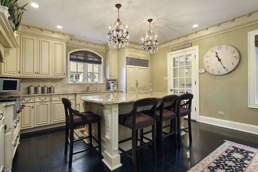 A kitchen with dark hardwood floors and beige walls. It offers a gorgeous center island with a breakfast bar, lighted by gorgeous chandeliers.