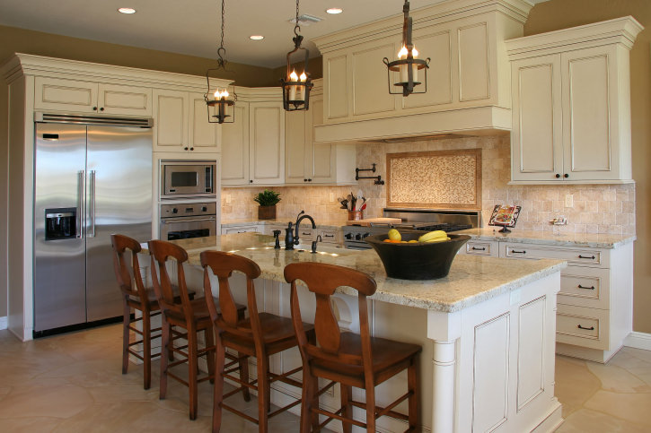 Kitchen with white cabinetry and kitchen counter, along with a white island featuring a marble countertop and has a breakfast bar.