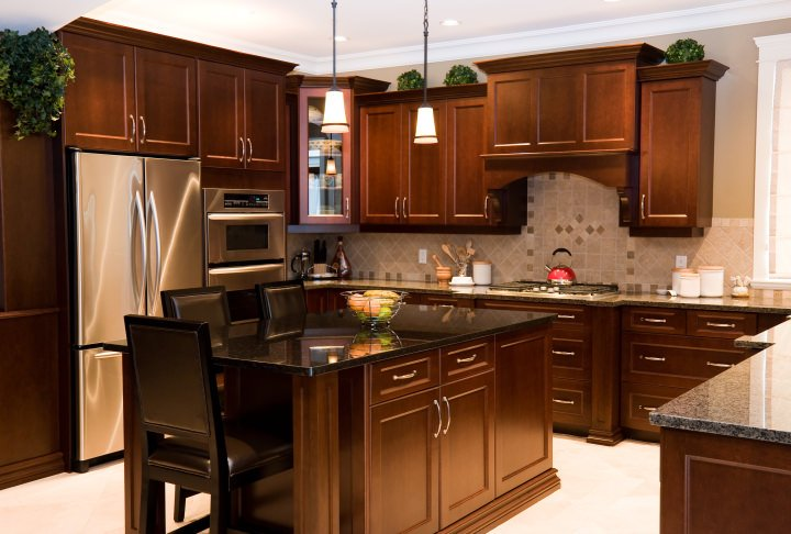 This kitchen has brown cabinetry and kitchen counters, along with a center island featuring a breakfast bar. This kitchen has granite countertops as well.