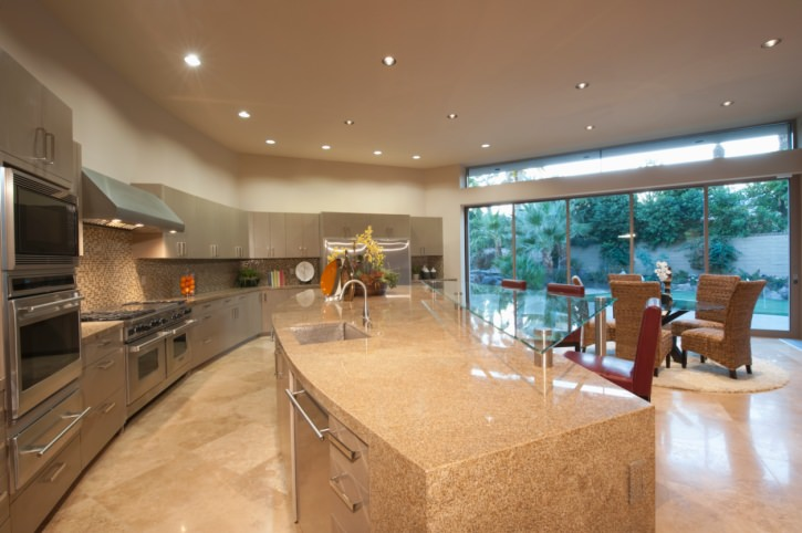 Spacious modern kitchen with a large island with a glass breakfast bar counter, along with an elegant dining table and chairs set on the side.