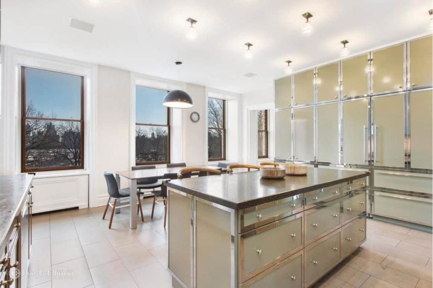 Modern dine-in kitchen featuring elegant cabinetry and kitchen counters. It offers a breakfast bar island and a rectangular dining table set.