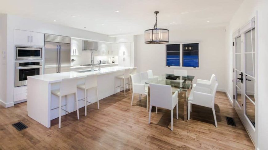 A dine-in kitchen featuring a white ceiling, white walls and hardwood flooring. It offers a long white breakfast bar island and a glass top dining table paired with white chairs.
