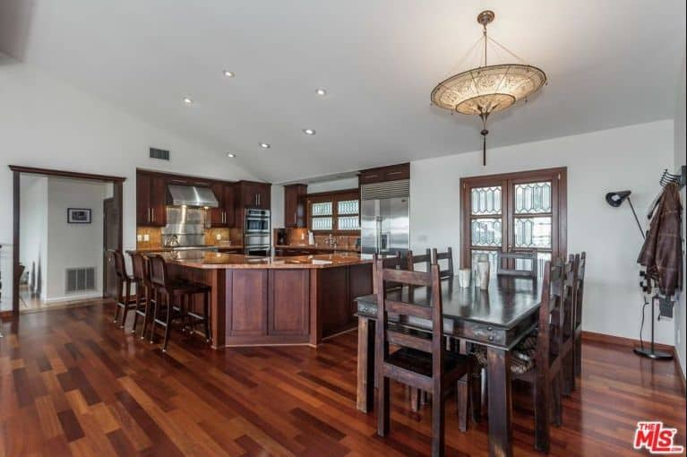 A spacious dine-in kitchen featuring hardwood floors and a white ceiling. It has a G-shaped kitchen counter with a breakfast bar along with a classy dining table set lighted by a charming pendant light.