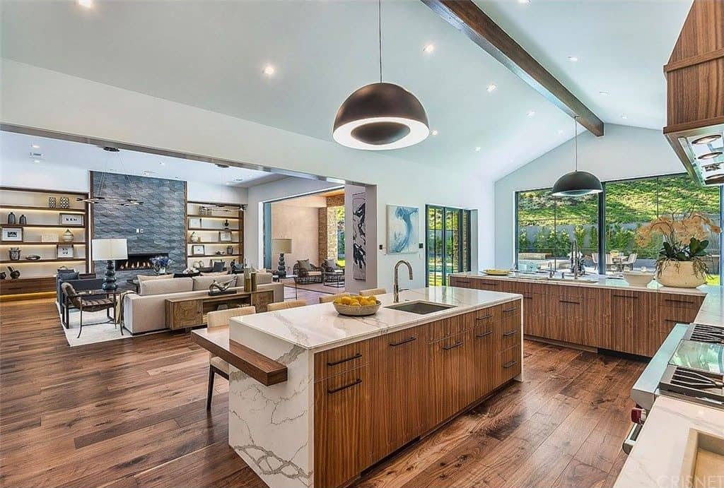 This great room features hardwood flooring and a white ceiling. The kitchen offers an L-shaped counter and a marble waterfall-style center island with a separate counter for breakfast bar.