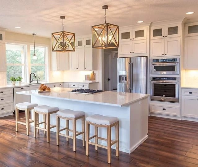 A spacious kitchen featuring hardwood flooring and enchanting pendant lights. It offers a white breakfast bar island set underneath the pendant lights.