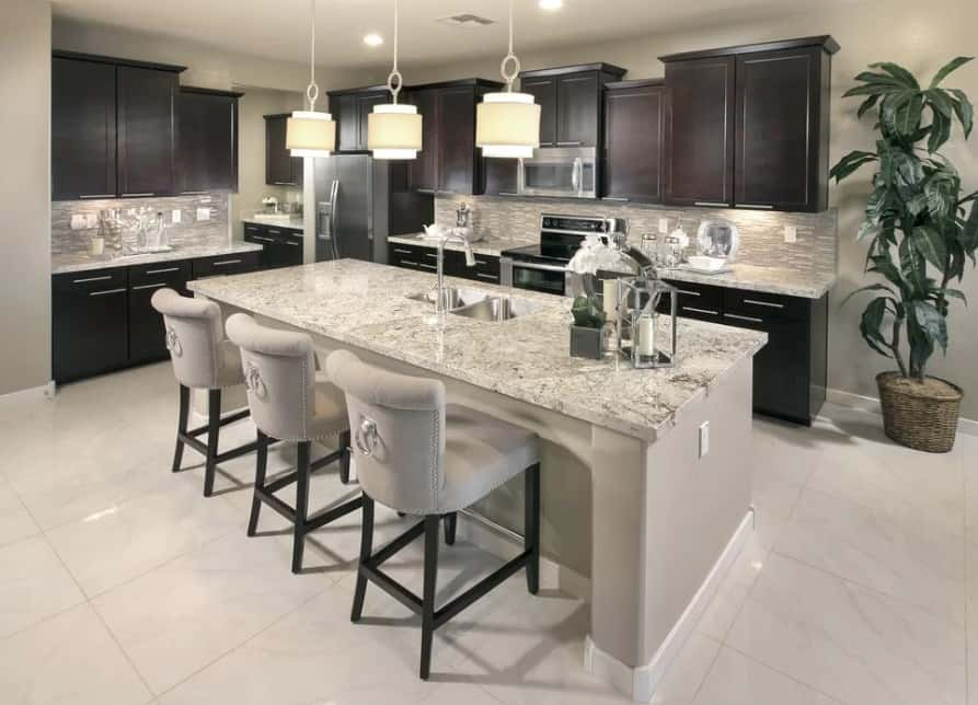 L-shape kitchen featuring dark brown kitchen counters and cabinetry, along with a marble breakfast bar island lighted by charming pendant lights.