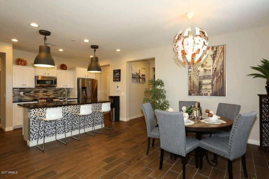 A dine-in kitchen boasting a stylish breakfast bar island and a classy round dining nook with gray chairs and is lighted by a very attractive pendant light.