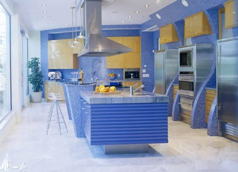 A modern kitchen boasting tiny blue tiles walls and backsplash, along with blue center island with a separate breakfast bar counter.