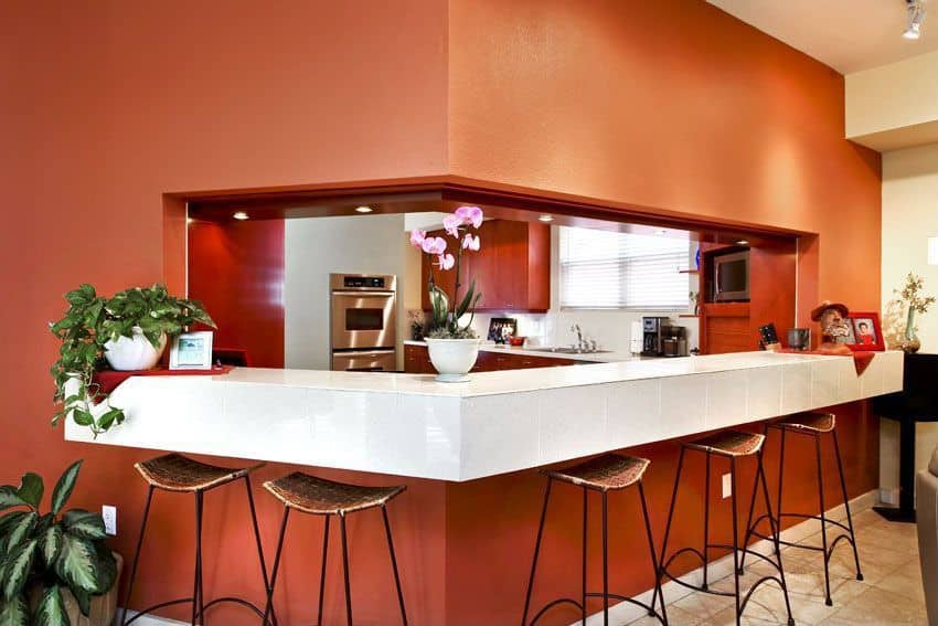 This galley kitchen boasts a white breakfast bar counter surrounded by the kitchen's orange walls.