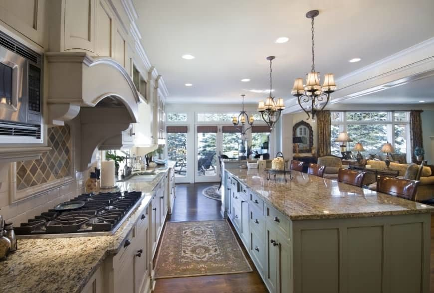 A large single wall kitchen boasting a massive center island with granite countertop and has a breakfast bar lighted by charming chandeliers.