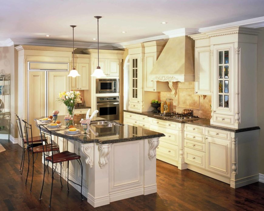 L-shaped kitchen featuring white kitchen counters and a white center island, both with black granite countertops.