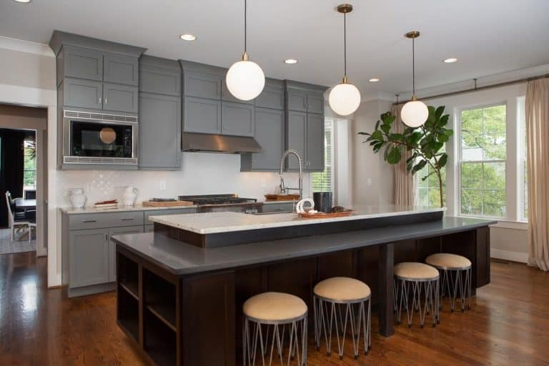 A single wall kitchen with gray cabinetry and cabinets, along with a custom center island with a preparation counter and a breakfast bar counter, lighted by pendant lights.