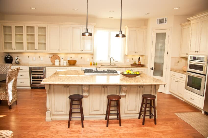 A dine-in kitchen boasting a center island with a breakfast bar lighted by pendant lights. The dining table set is placed on the side of the area.
