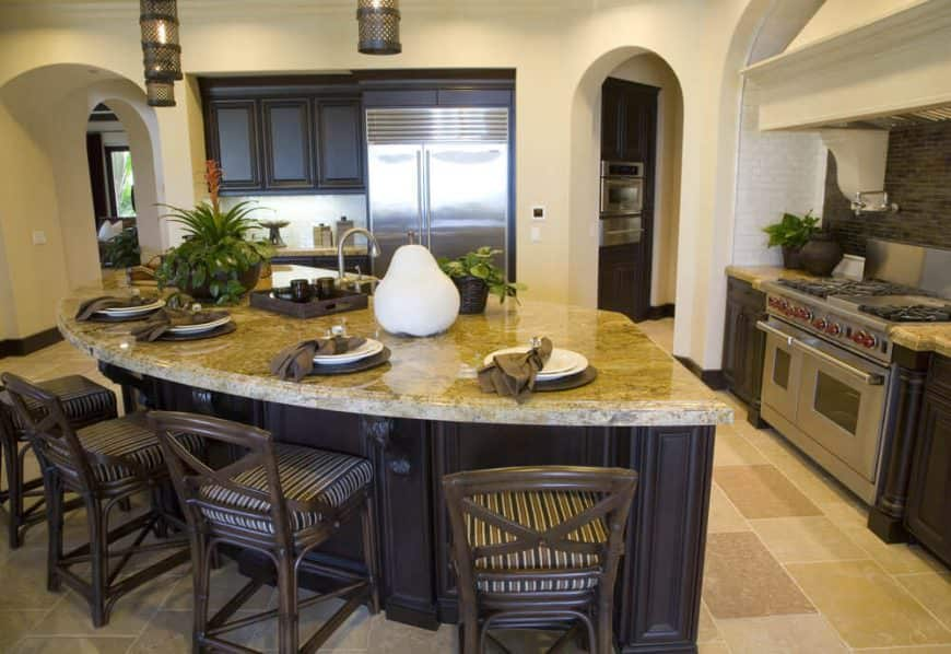 This kitchen features a custom made island with a marble countertop and has space for a breakfast, lighted by pendant lights.