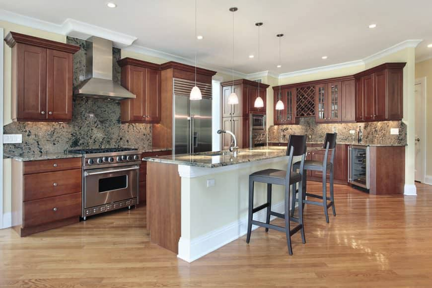 This kitchen features wood tone kitchen counters and cabinetry, along with a marble countertop center island with a breakfast bar for two.