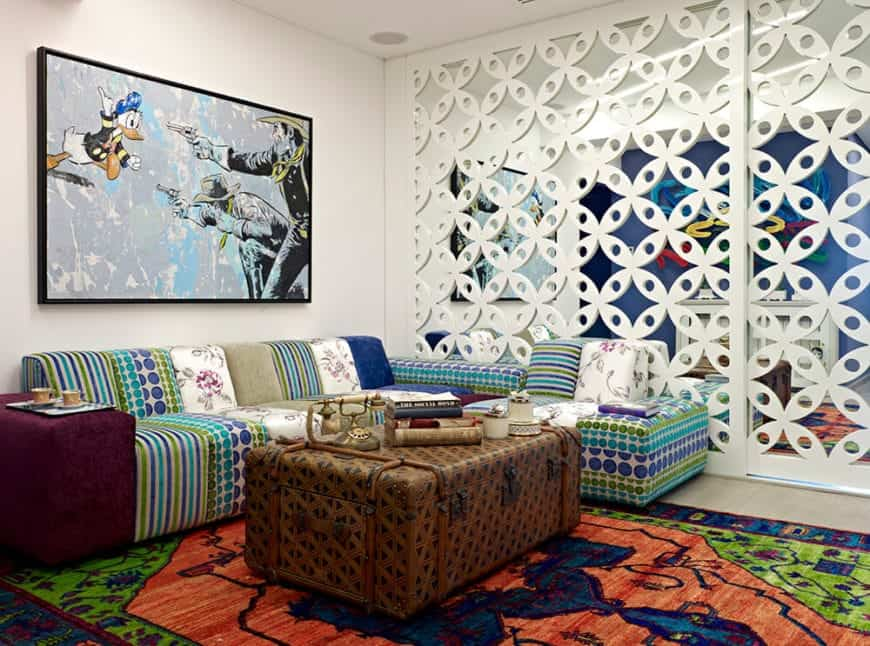 This living room is decorated with a large artwork that hung above the L-shaped sofa paired with a storage chest coffee table. It has a stylish mirrored wall and beige flooring topped by a multi-colored rug.