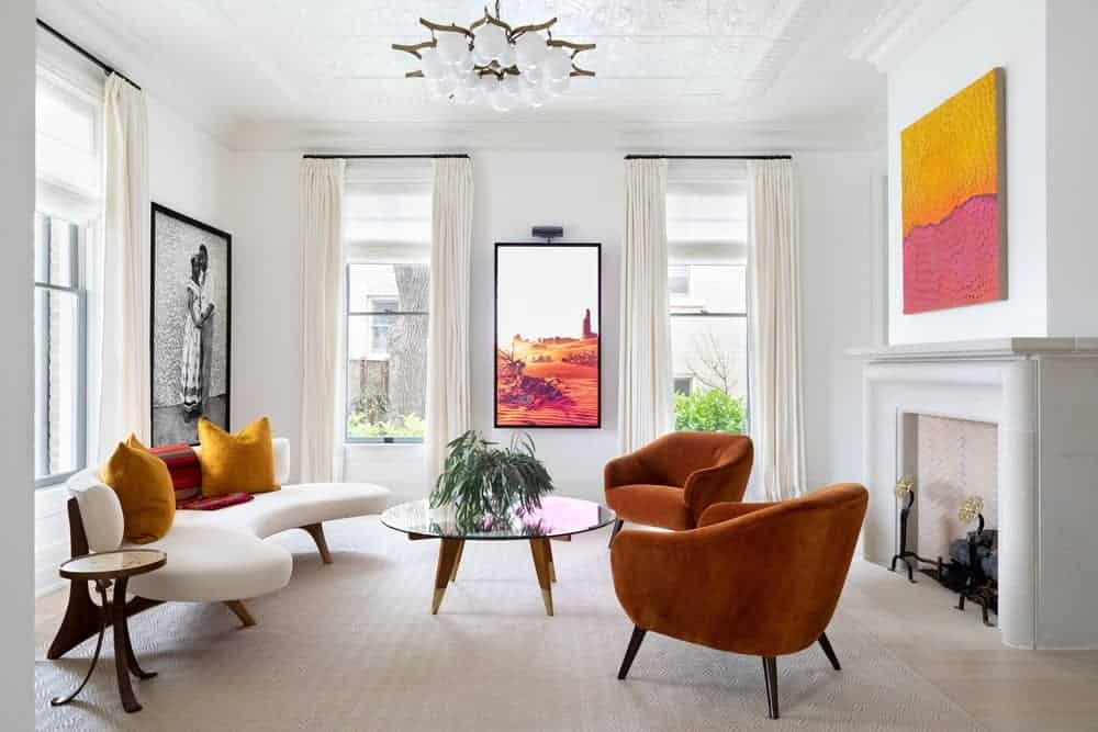 Light and airy living room decorated with gorgeous artworks and a lovely chandelier that hung over the glass top coffee table surrounded by cozy seats. It has a fireplace and glazed windows bringing an abundance of natural light in.