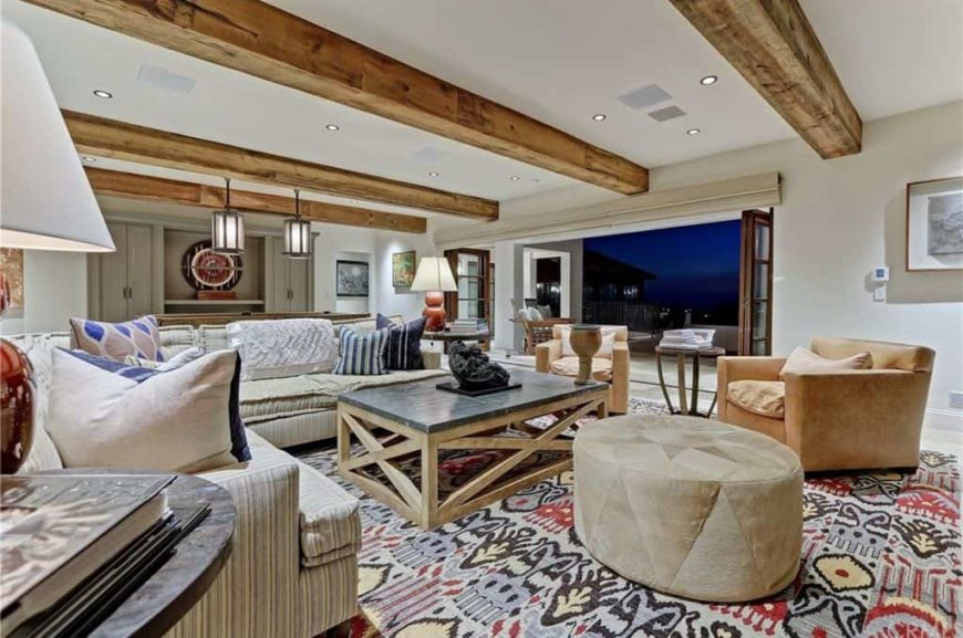 A spacious living room boasting comfy seats and a large area rug set under the home's ceiling with large exposed beams.