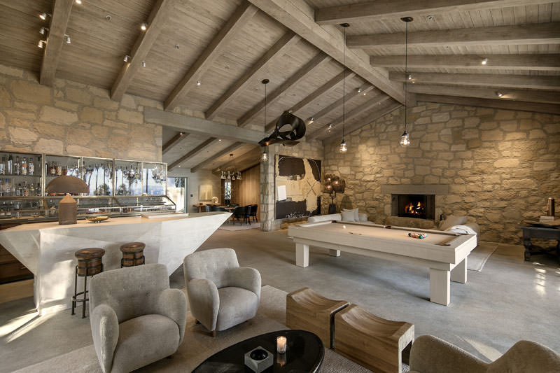 A massive man cave with a living space, a bar area and a billiards table lighted by pendant lights hanging from the tall wooden vaulted ceiling with exposed beams.