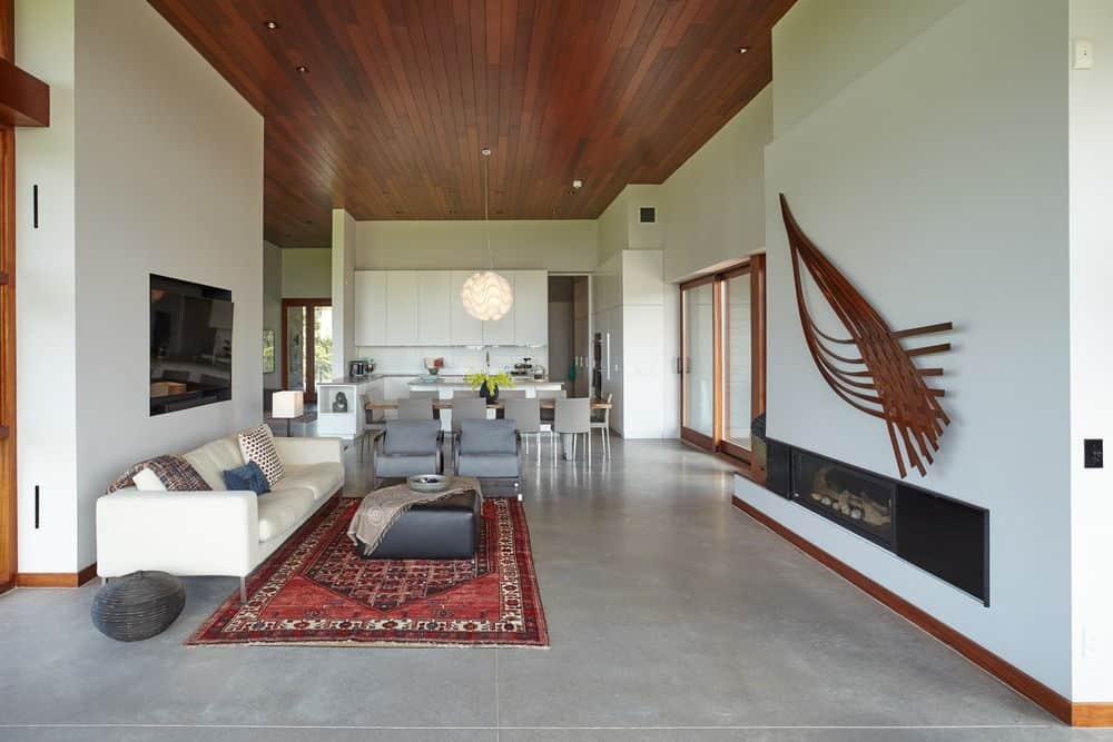 A great room with gray tiles flooring and a tall wooden ceiling. It has a white sofa and a gas fireplace.