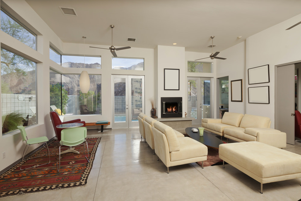 Modern living room with a modern beige sofa set along with a fireplace and glass windows. The home also features large tiles flooring.
