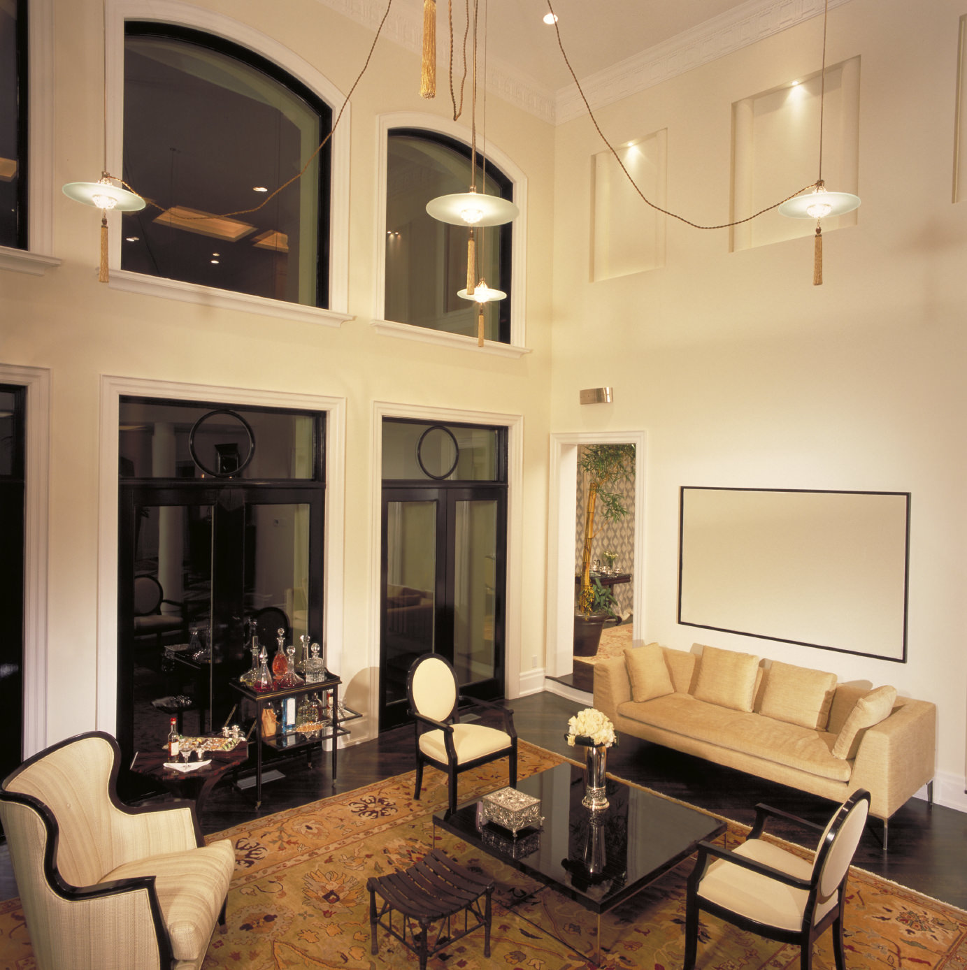A formal living room featuring glass doors and windows, along with a tall ceiling. The room offers classy set of seats and a large brown area rug.