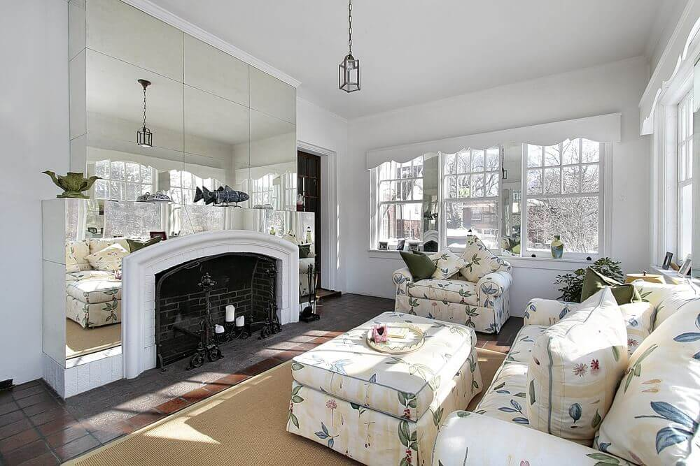 Large living room offering a gorgeous set of seats with a large ottoman, along with a large fireplace.