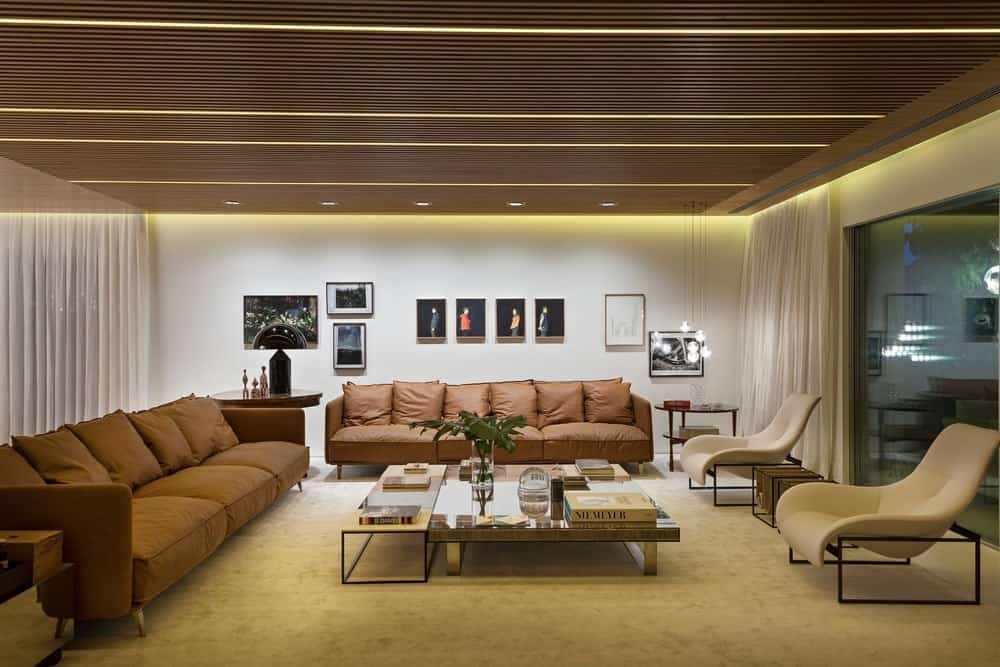 Modern living space featuring a stunning ceiling along with carpeted flooring. The room offers a pair of modern brown sofa set and a stylish center table.