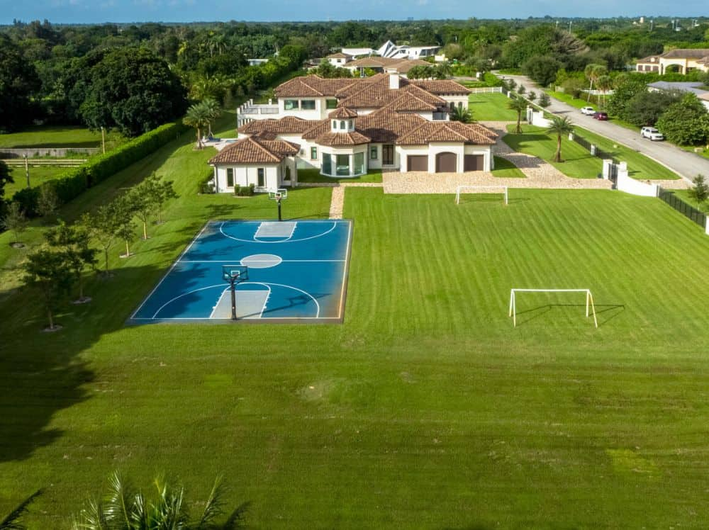 This is an aerial view of the house with multiple structures, white exterior walls and red clay roofs complemented by the lush landscaping of spacious grass lawns and sports areas.