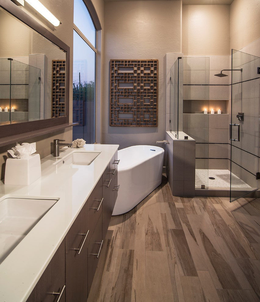 A wooden wall art complementing the floating vanity hangs above the freestanding tub by the glazed window. It is accompanied by a walk-in shower and a rectangular mirror lighted by a linear sconce.