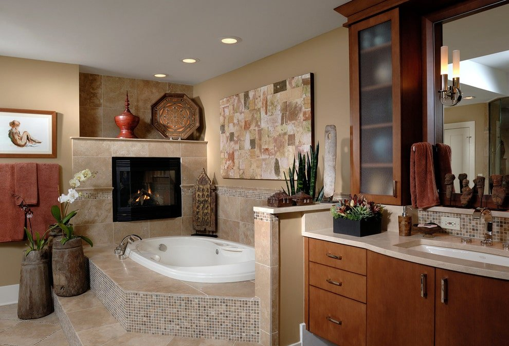 Sophisticated primary bathroom decorated with wooden vases and interesting paintings mounted on the beige walls. It has a wooden sink vanity and a whirlpool tub with a black fireplace on top adding warmth in the room.