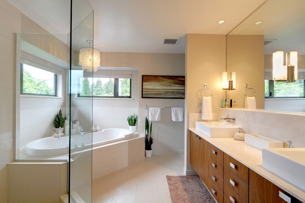 This primary bathroom offers a walk-in shower and a drop-in tub illuminated by a shell chandelier. It includes small potted plants and a wooden vanity topped with his and her vessel sinks.