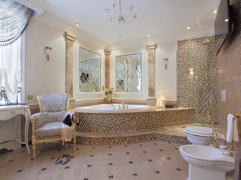 Luxury master bathroom designed with stylish mirrors and a fancy crystal chandelier that hung over a corner tub clad in stunning mosaic tiles. It is accompanied by a patterned armchair and toilets under a wall-mount TV.