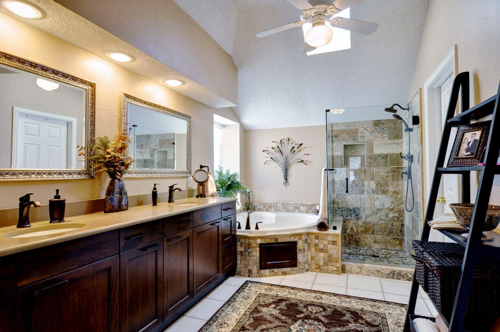 Traditional master bathroom with a black shelving unit and a dark wood vanity adjacent to the corner tub and walk-in shower. It is decorated with floral wall art and a classic area rug that lays on the white tiled flooring.