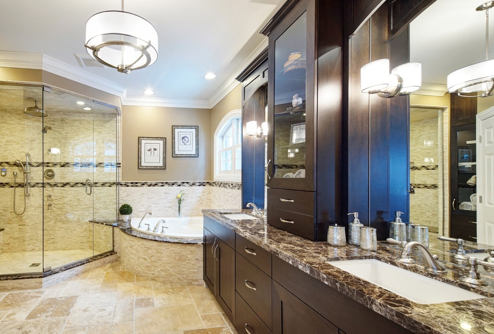 A drum chandelier illuminates this master bathroom showcasing a corner tub that's fixed in between the walk-in shower and dark wood his and her sink vanity. It has limestone flooring and beige walls mounted with framed artworks.
