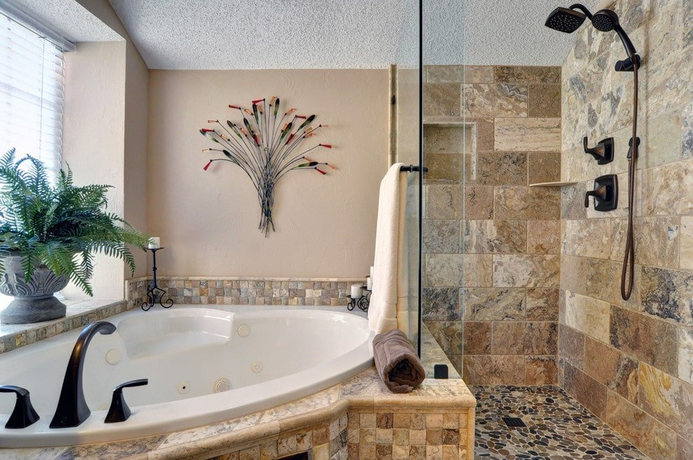 A corner tub accented with a lovely wall art sits next to the walk-in shower with wrought iron fixtures. It has pebble flooring and brick backsplash fitted with an inset shelf.