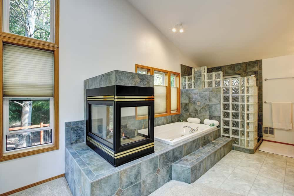 A three-sided fireplace accented with gold trims adds warmth in this master bathroom with a deep soaking tub and wooden framed windows allowing natural light in.