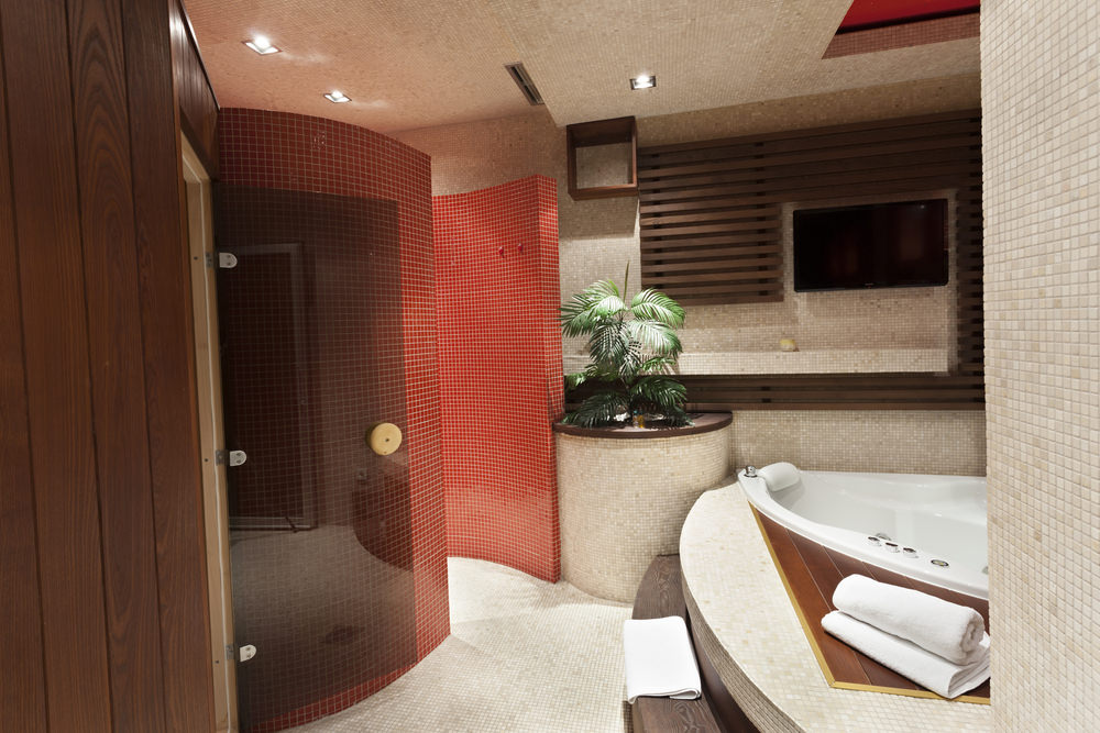 Deluxe master bathroom with a drop-in tub and a walk-in shower enclosed in curved walls that are clad in red mosaic tiles. There's a palm plant in the middle creating a tropical feel in the room.