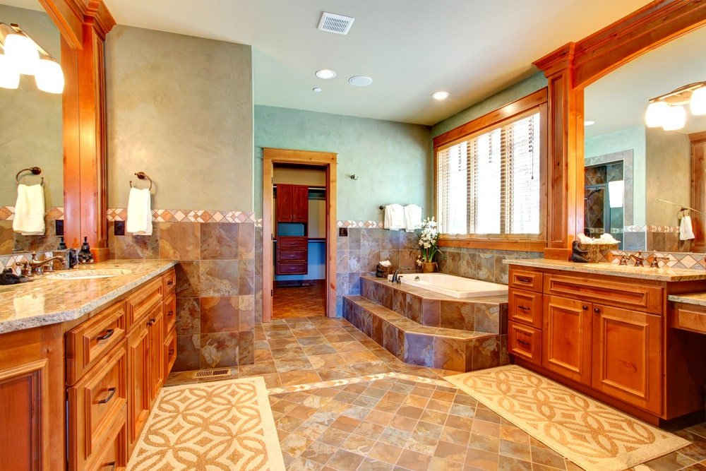 Warm master bathroom with a deep soaking tub and wooden vanities facing each other. It is paired with patterned rugs that lay on the limestone flooring.