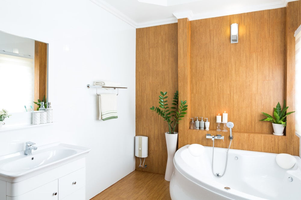 Fresh potted plants add a nice accent in this master bathroom with white sink vanity and a whirlpool tub that goes well with the wooden paneled wall and hardwood flooring.