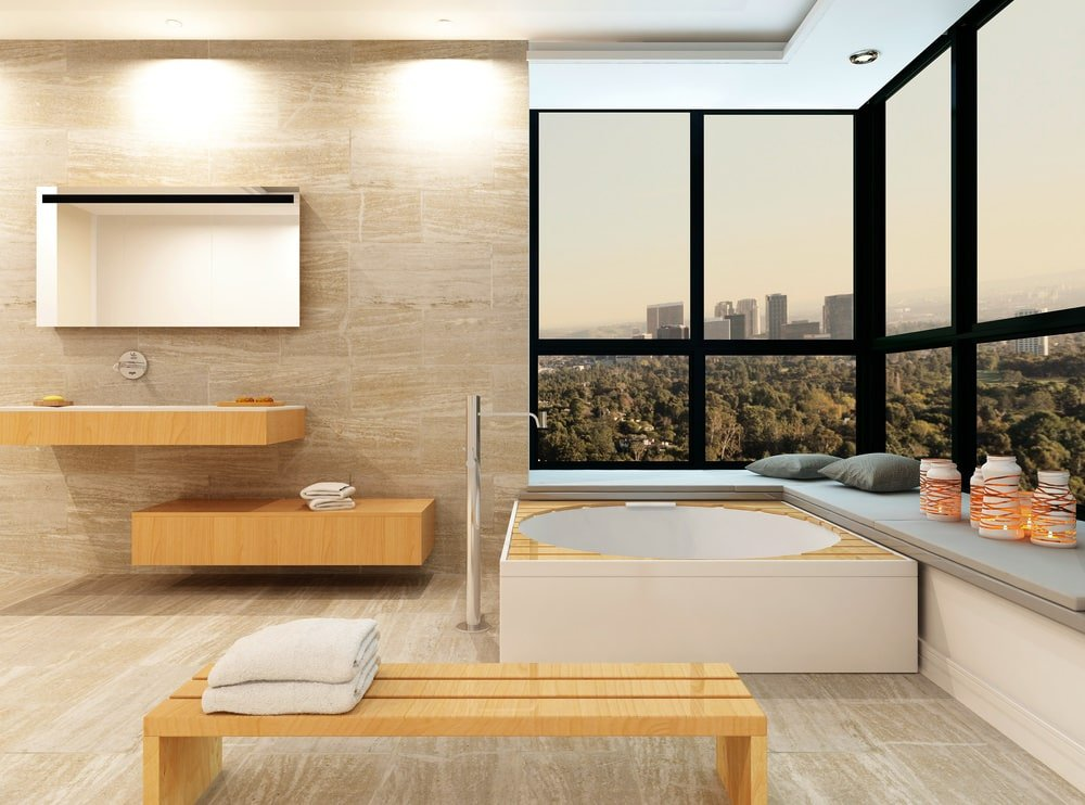 A wooden bench matches the floating shelves that are mounted under a mirrored medicine cabinet. It is accompanied by a corner tub situated on the window seat nook overlooking the outdoor scenery.