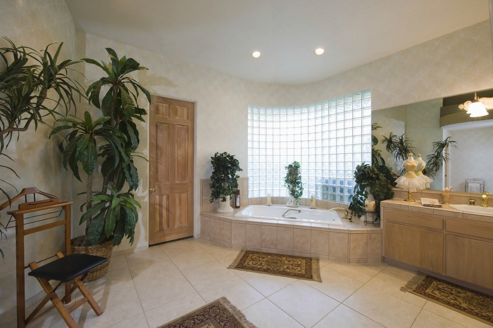 Green potted plants create a tropical feel in this master bathroom with a deep soaking tub and a light wood sink vanity paired with a frameless mirror. It has a glass block window and beige tiled flooring topped by tasseled rugs.