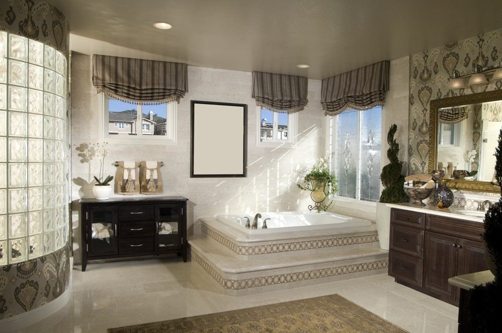 A black cabinet creates a striking contrast to the drop-in tub that blends in with the walls and flooring topped by a classic area rug. It is accompanied by a wooden vanity and glazed windows dressed in striped roman shades.