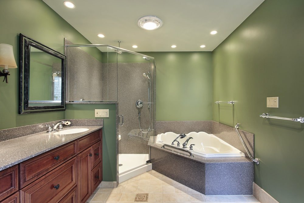 Green master bathroom illuminated by flush and recessed lights mounted on the regular white ceiling. It has a corner tub, a walk-in shower and a wooden sink vanity that's paired with a black framed mirror.