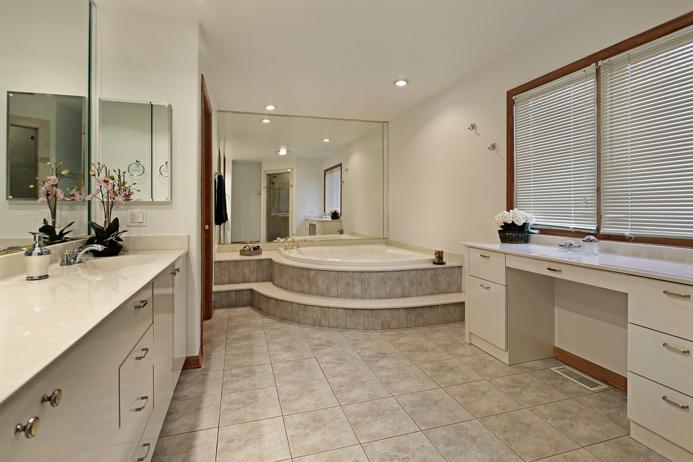 Spacious master bathroom with beige tiled flooring and wooden framed windows covered with white roller blinds. It includes facing vanities and a corner tub by the mirrored wall.