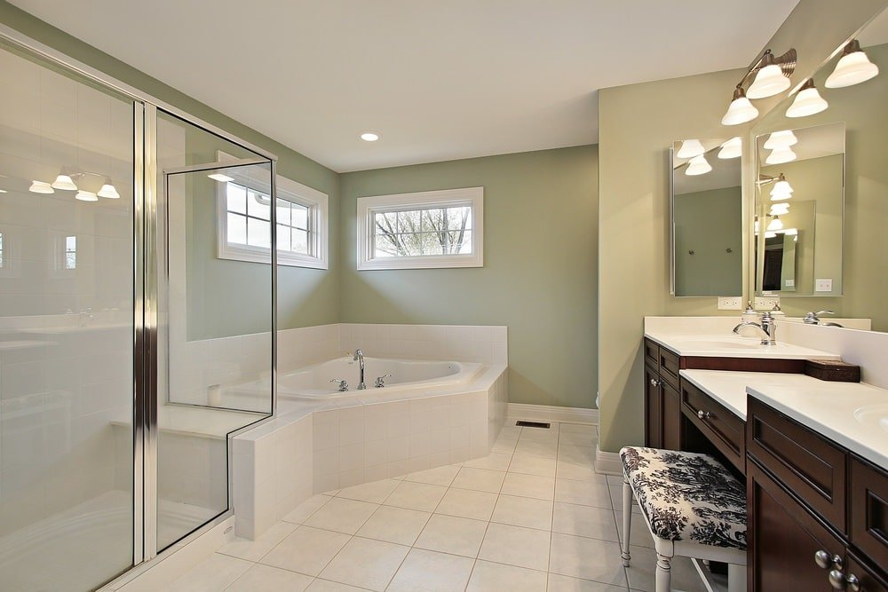 Glass sconces illuminate the dark wood vanity showcasing a double sink and a cushioned stool. It is accompanied by a walk-in shower and a corner tub against the sage green walls.