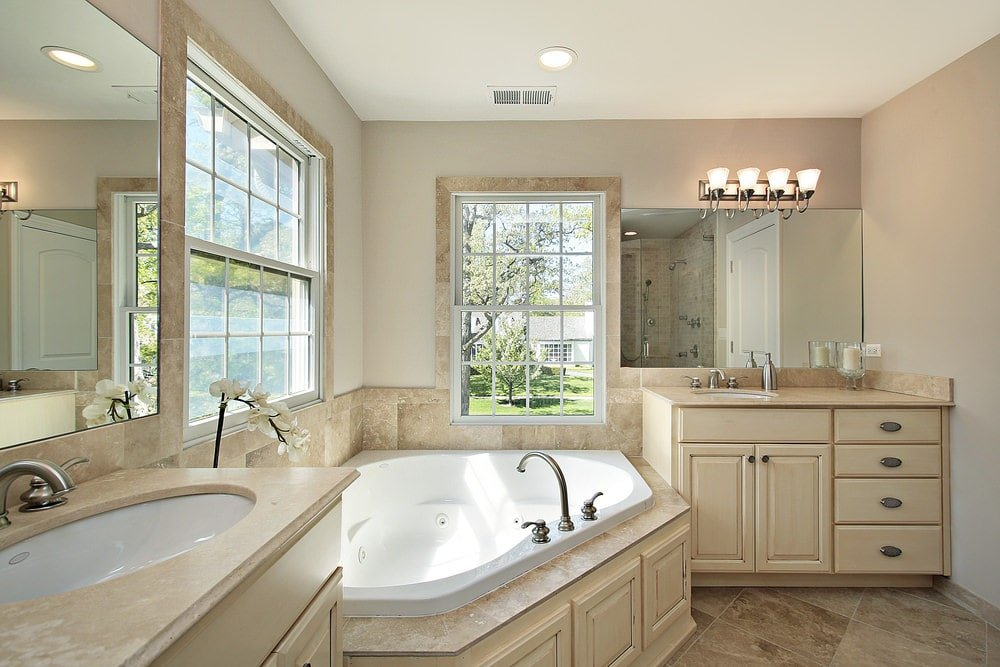 Light wood vanities under frameless mirrors flank a corner tub by the white framed windows inviting natural light in. It is lighted by glass sconces mounted on the beige walls.